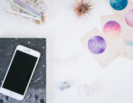 Constellation cards next to notebook and iphone on white table