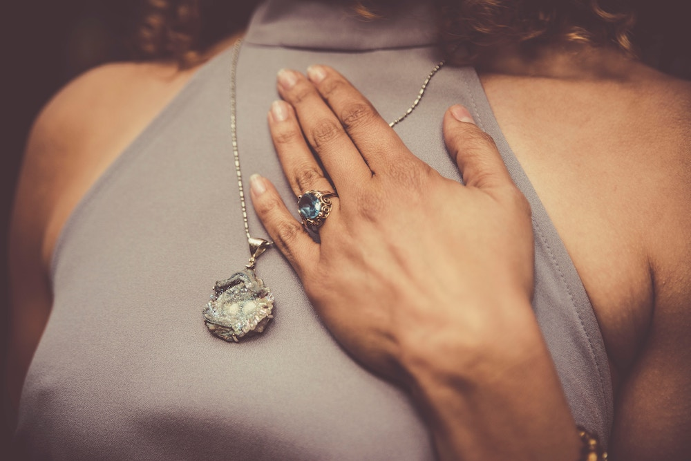 Woman placing hand over her heart wearing blue ring and crystal necklace